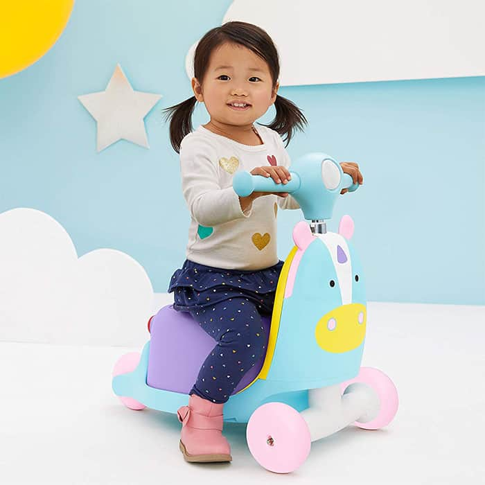 little girl on a skip hop unicorn ride on
