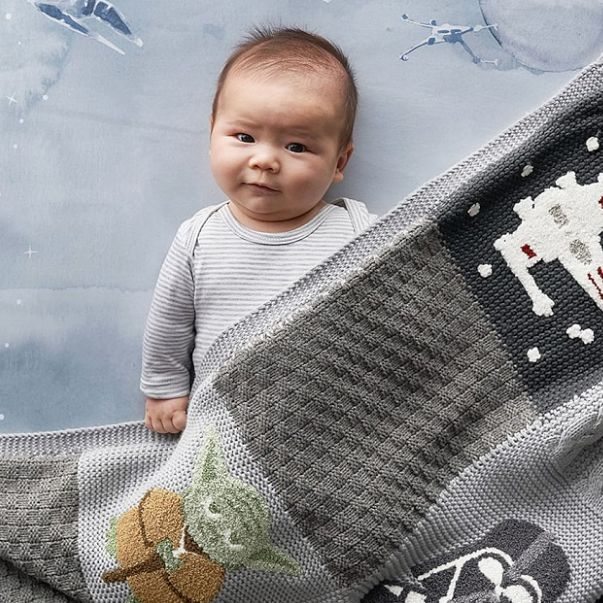 Baby laying under Star Wars themed baby quilt featuring Yoda, Darth Vader and an X-Wing