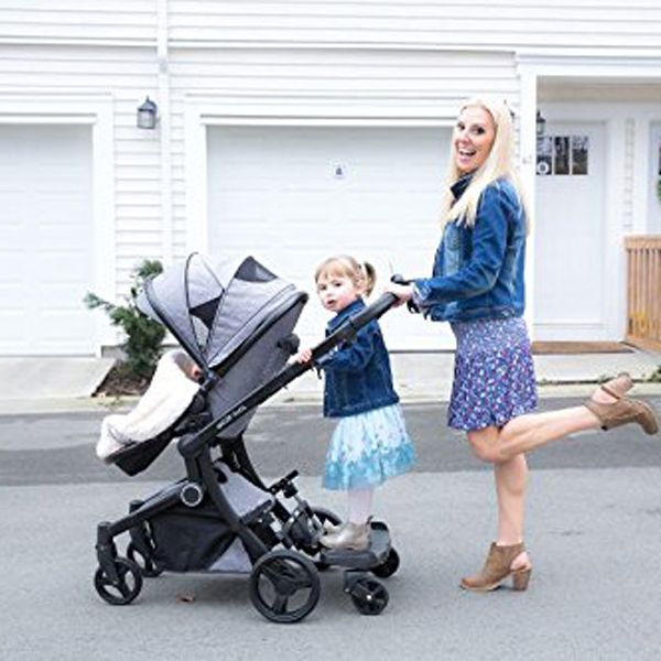 toddler riding on stroller board with mom pushing stroller