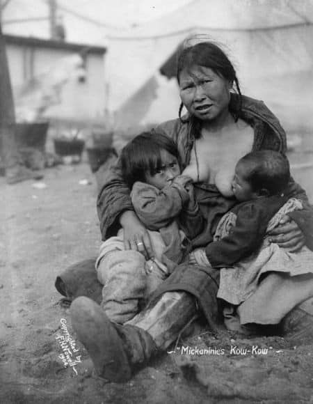 Black and white old photograph of Indigenous woman tandem nursing children outdoors in Alaska