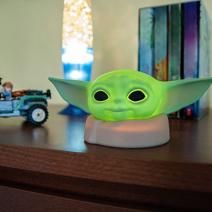 "Green Baby Yoda ""The Child"" nightlight lit up on a child's bookshelf"