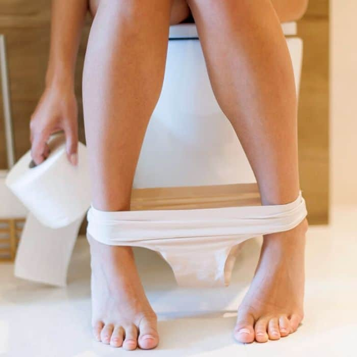 feet of woman sitting on the toilet while holding toilet paper