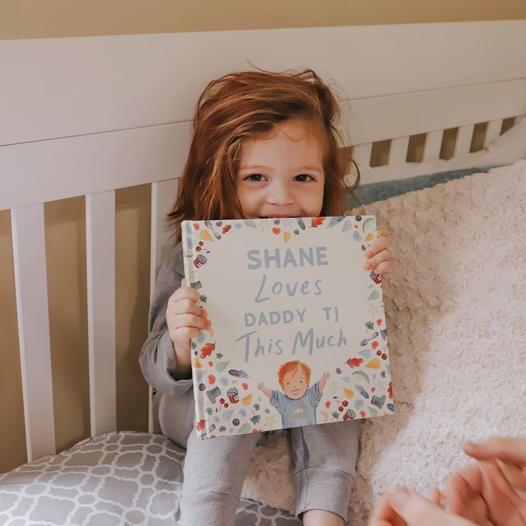 child holding a custom 'dad' book for father's day.