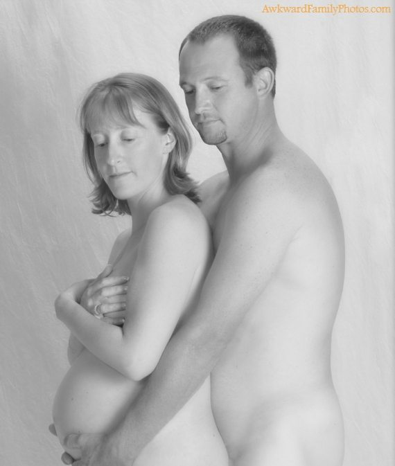 Fully nude couple spoons while she covers her breasts with her hands and he cradles her bump.