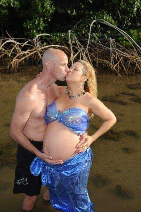 Photo of topless man and woman dressed as a mermaid standing in a swamp kissing while he cradles her bare bump.