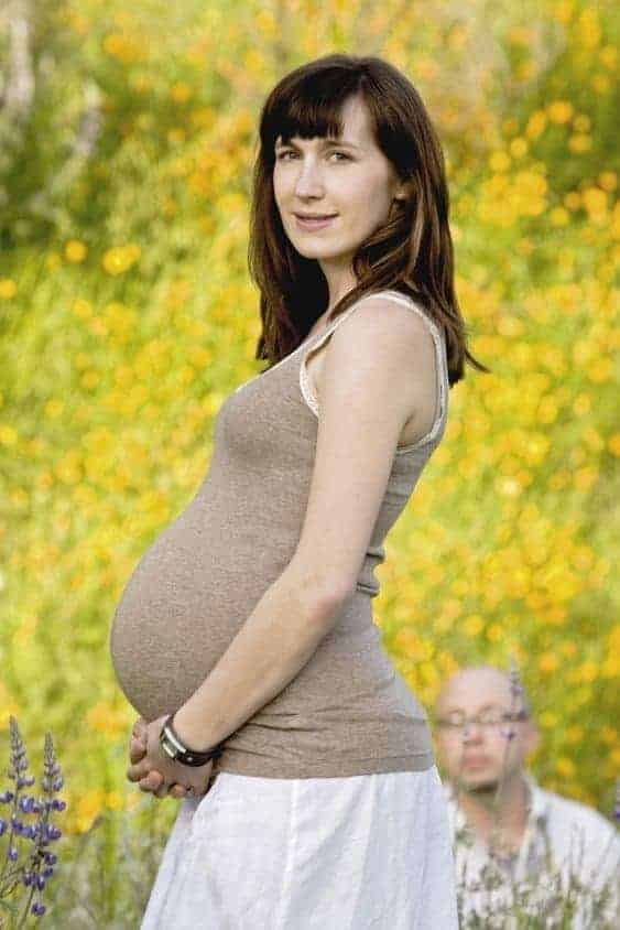 Pregnant woman stands in field of wildflowers while bald man crouches in the background
