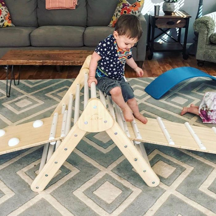 baby climbing on Pikler triangle