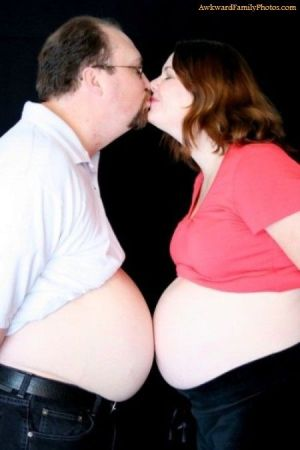 Couple stands and kisses while bare bumps touch.
