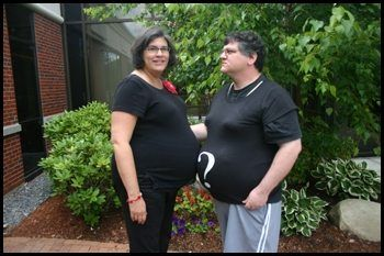 Couple stands facing one another. Both wear black t-shirts, hers plain, his with a question mark on it.
