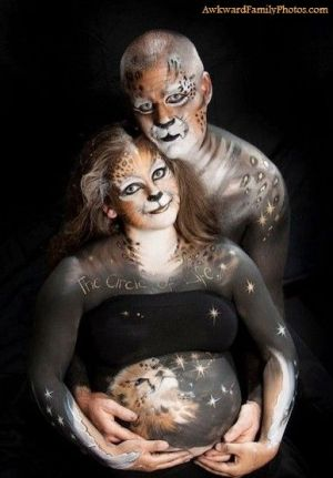 Couple in full body paint designed to make them look like Cheetahs in space face the camera while he cradles her bare bump.