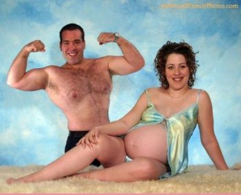 Couple faces the camera, he, standing behind his pregnant partner, topless and flexing, she sitting and smiling while her shirt exposes her bare bump.