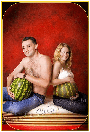 Couple sits back to back smiling at camera. He is topless cradling a watermelon, she is wearing a white tank top and has her bump painted like a watermelon.