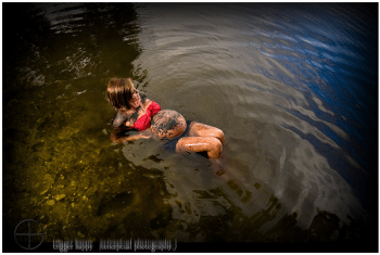 Woman lays in muddy river with red top, black shorts, and mud smeared all over her belly.