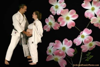Left side of photo shows two people dressed in white martial arts robes facing each other while he places a hand on her bare bump. Right side of photo shows pink and white dogwood flowers